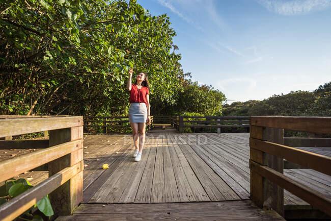 Молода жінка, яка в сонячний день стоїть на дерев