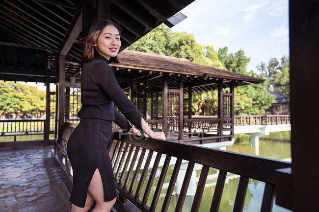 Side view of cheerful Asian female in black clothes standing on fenced terrace near green river and forest while looking at camera in daylight — Stock Photo