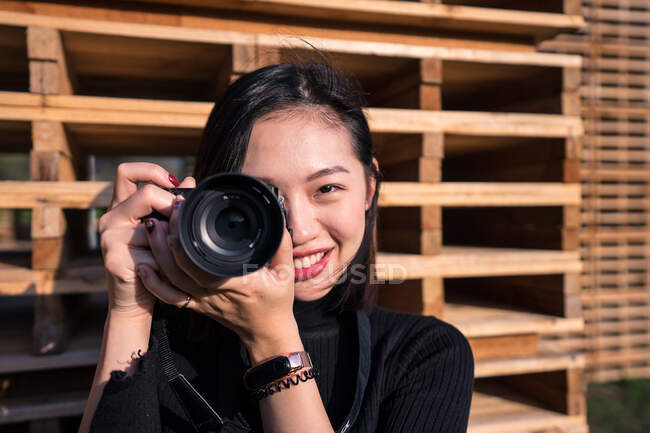 Cheerful young Asian female photographer in casual wear and wristwatch taking photo on digital photo camera while standing near wooden fence and looking at camera — Stock Photo