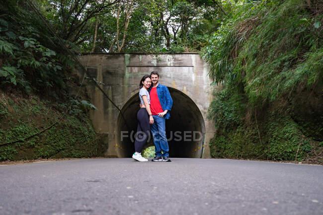 Felice coppia multirazziale in abbigliamento casual coccole e guardando la fotocamera mentre in piedi su strada asfaltata vicino al monte verde alla luce del giorno — Foto stock