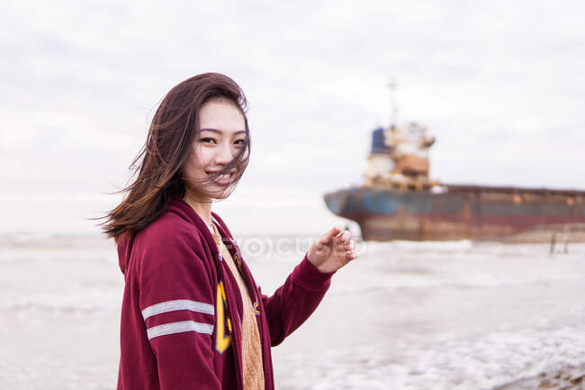 Side view of happy young Asian female in casual clothes standing on seacoast near old vessel and looking at camera on cloudy day — Stock Photo