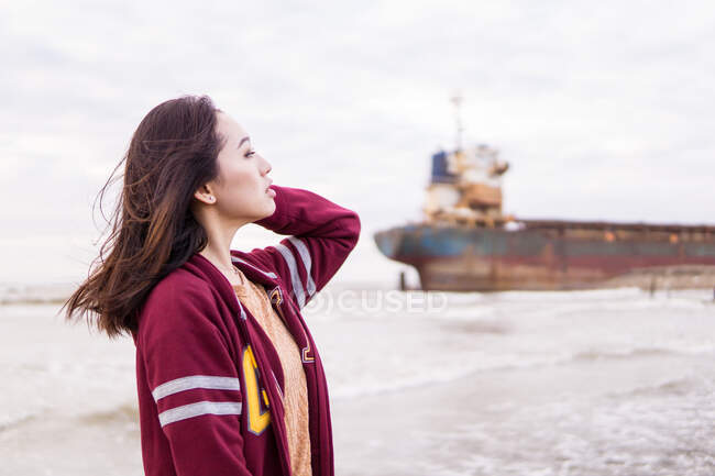Side view of happy young Asian female in casual clothes standing on seacoast near old vessel and looking away on cloudy day — Stock Photo