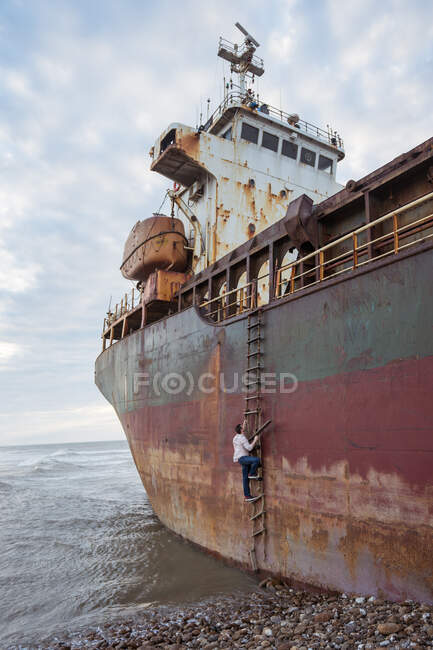 Side view of anonymous male in casual wear and sneakers climbing ladder of shabby and rusty ship located on sea beach in daylight — Stock Photo