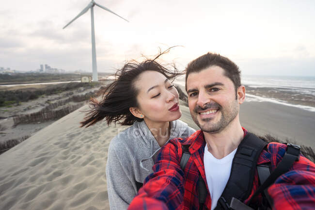 Весела багаторасова пара у повсякденному одязі обнімається, а під час подорожі під хмарним небом стоїть на піску і дивиться на камеру. — стокове фото