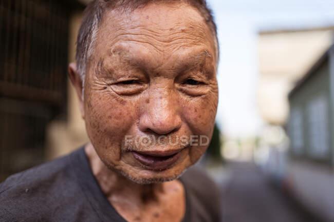 Porträt eines älteren asiatischen Gärtners in lässiger Kleidung, der auf der Straße in einer Siedlung in Taiwan in die Kamera lächelt — Stockfoto