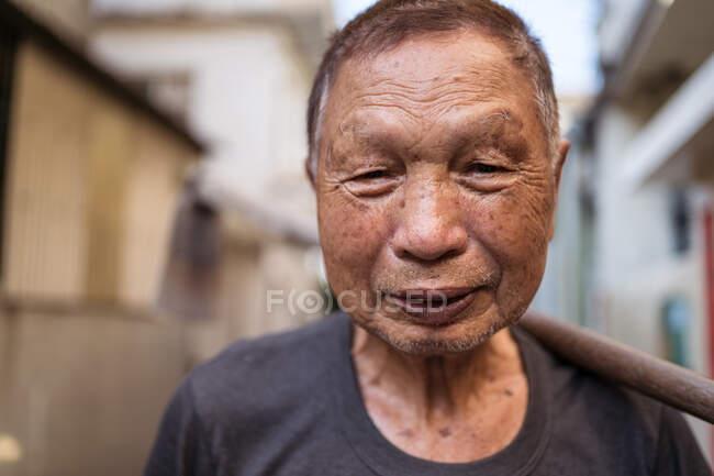 Porträt eines älteren asiatischen Gärtners in lässiger Kleidung, der in Taiwan mit Hacke über Schulter auf der Straße steht und in die Kamera lächelt — Stockfoto