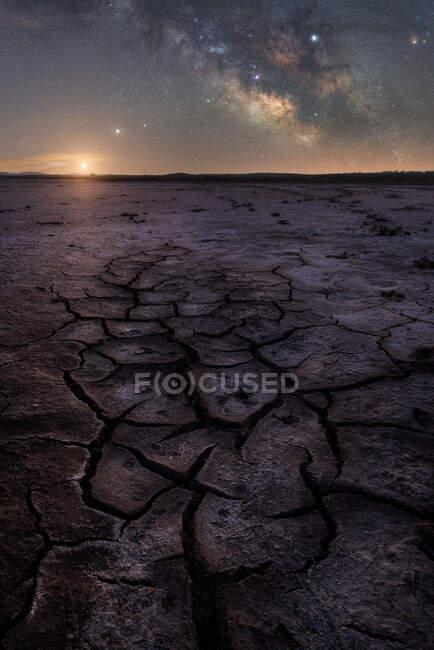 Superfície rachada seca do céu estrelado da terra e da noite colorida no horizonte — Fotografia de Stock
