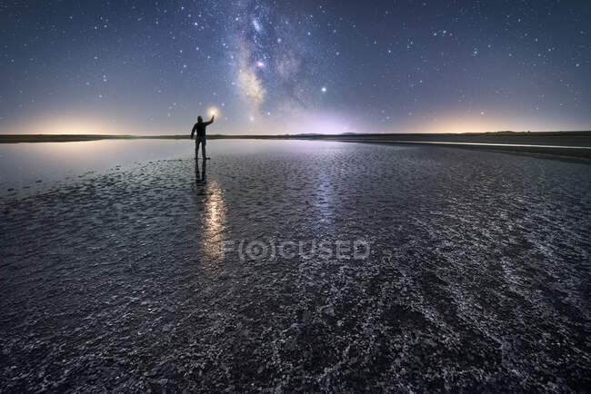 Back view of anonymous man standing and holding torch on empty road among calm water and reaching out to star under colorful nigh sky with milky way on background — Stock Photo