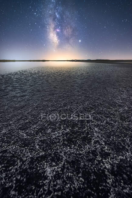 Empty dry soil among calm water under colorful nigh sky with milky way on background — Stock Photo