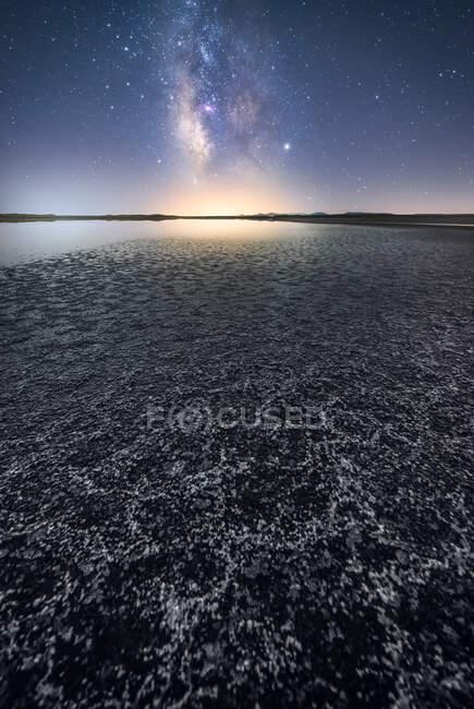 Пустой сухой почве среди спокойной воды под красочным небом с молочным путем на заднем плане — стоковое фото