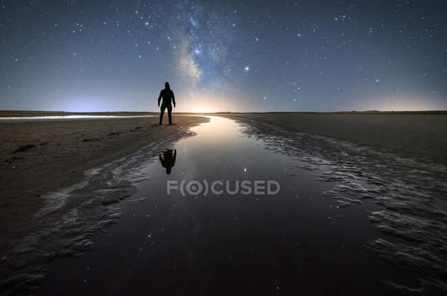 Vue arrière de l'homme anonyme debout sur une route vide au milieu de l'eau calme et tendre la main à l'étoile sous un ciel proche coloré avec la voie laiteuse sur fond — Photo de stock