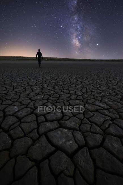 Silhueta de homem irreconhecível em pé sobre a superfície seca rachada do solo, estendendo-se para um colorido céu estrelado noturno no horizonte — Fotografia de Stock