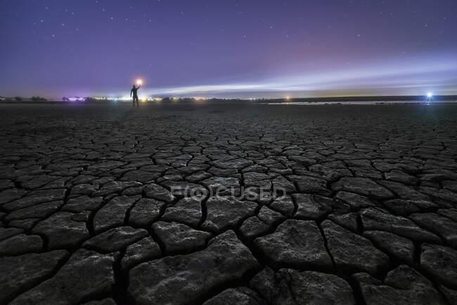 Silhueta de homem irreconhecível de pé com tocha na mão sobre a superfície seca rachada do solo estendendo-se para um céu estrelado noite colorida no horizonte — Fotografia de Stock