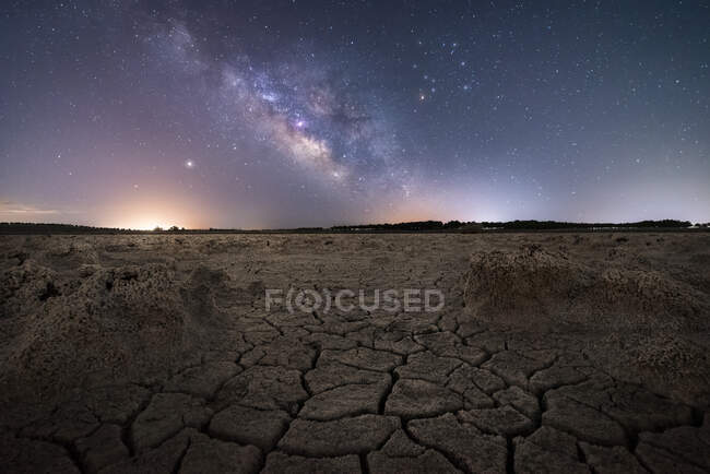 Dry cracked surface of ground and colorful night starry sky on horizon — Stock Photo