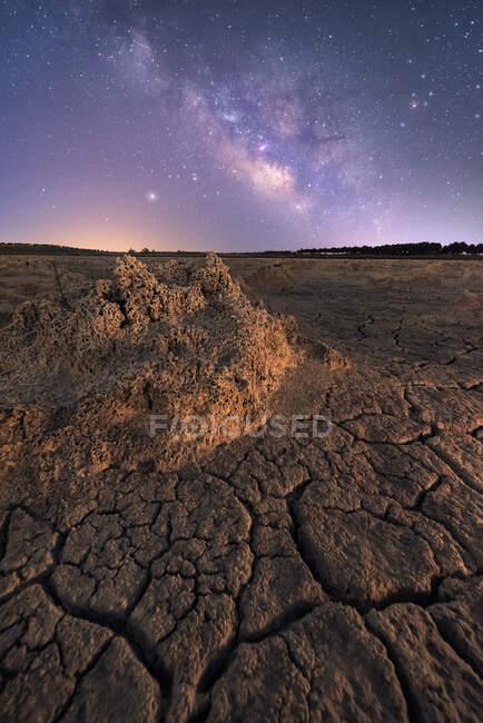 Surface fissurée sèche du sol et ciel étoilé nocturne coloré à l'horizon — Photo de stock