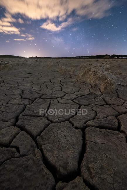 Seco rachado chão sem vida sob céu nublado colorido ao pôr do sol tempo — Fotografia de Stock