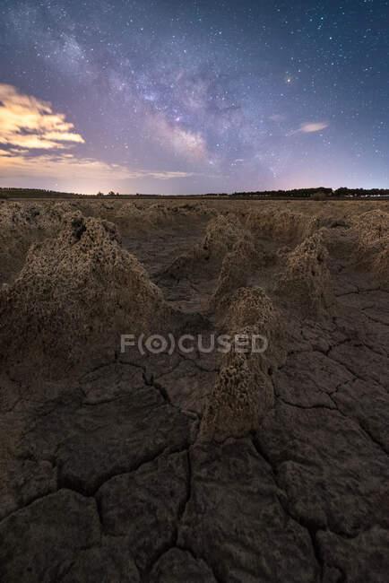 Sécheresse sol sans vie fissuré sous un ciel nuageux coloré au coucher du soleil — Photo de stock