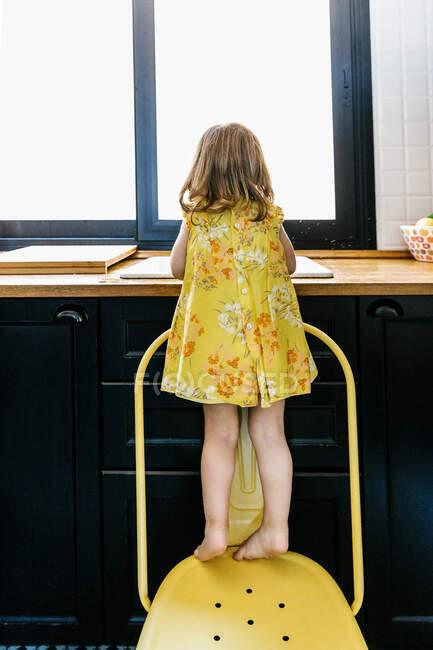 Полностью анонимная босиком девушка в желтом платье стоит на стуле возле кухонной раковины и моет руки об окно — стоковое фото
