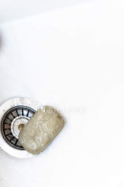 Вид сверху куска мыла, помещенного рядом с дренажом во влажную раковину под проливной водой — стоковое фото