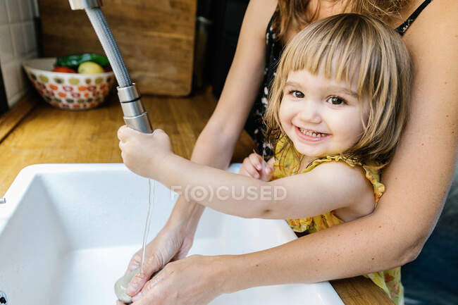 Delighted little girl smiling and looking at camera while washing hands with crop mother over sink in kitchen at home — Stock Photo