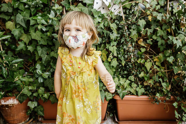 Full body barefoot girl in yellow dress and cloth mask looking at camera while standing near bushes in yard — Stock Photo