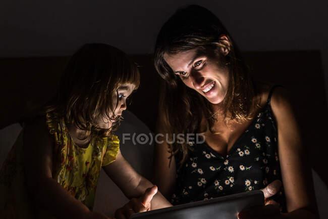 Donna allegra mostrando tablet alla ragazza stupita mentre seduto sul letto in camera da letto buio a casa — Foto stock