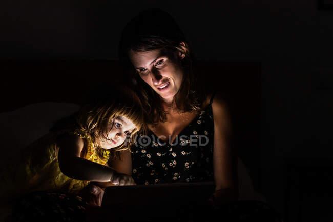 Donna che mostra tablet a ragazza stupita mentre seduto sul letto in camera da letto buio a casa — Foto stock