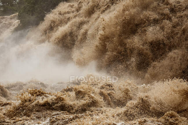 Dirty turbulent river stream with splashes of Awash Falls Lodge falling from waterfall in mountainous area — Stock Photo