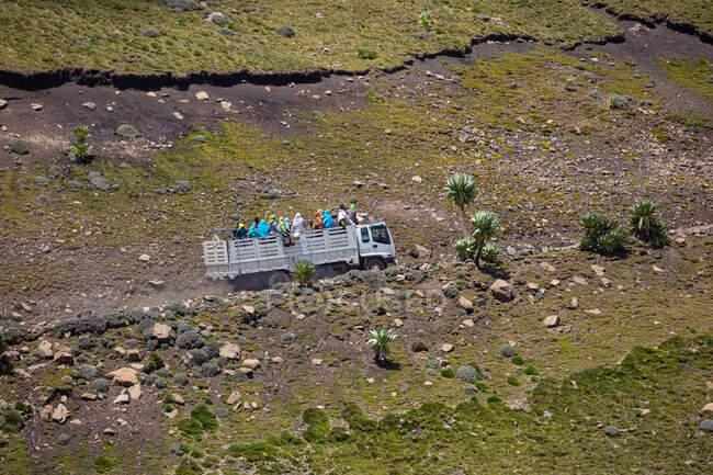 Vue de la vieille voiture avec des personnes dans la remorque conduisant le long de la route montagneuse — Photo de stock