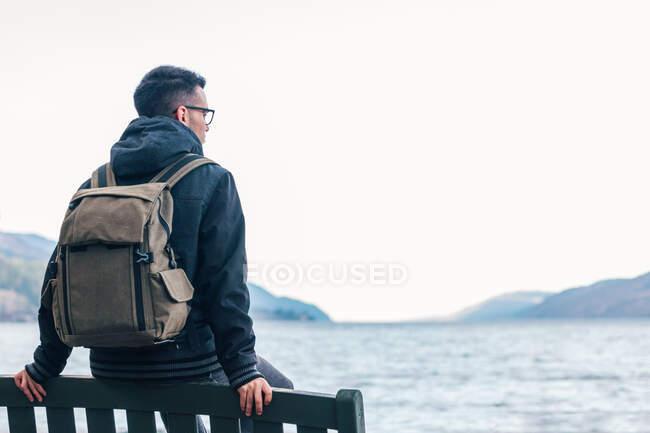 Vista posteriore dell'escursionista maschio in giacca calda con zaino seduto su una panchina di legno vicino al mare e godendo di paesaggi marini con costa rocciosa durante il viaggio in Scozia — Foto stock