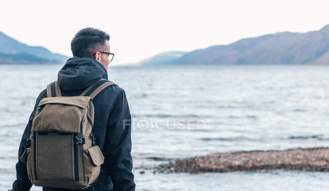 Back view of male hiker in warm jacket with backpack sitting on wooden bench near sea and enjoying marine scenery with rocky coast during travel in Scotland — Stock Photo