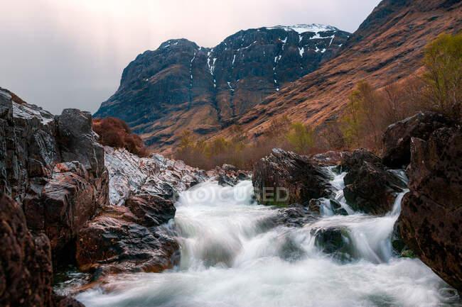 Грубый природный ландшафт с горной рекой, протекающей среди скалистых гор в облачный день в Шотландии — стоковое фото