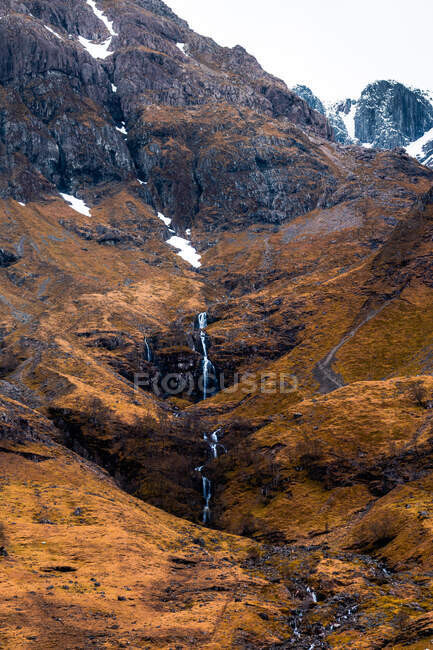 Rough rocky mountain slope with leafless bushes and waterfall in Scottish Highlands — Stock Photo