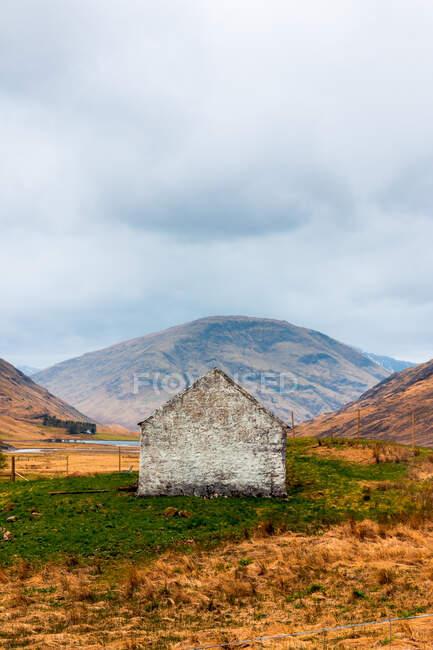 Casa de piedra envejecida situada en colina verde contra majestuosa montaña rocosa en las tierras altas escocesas - foto de stock