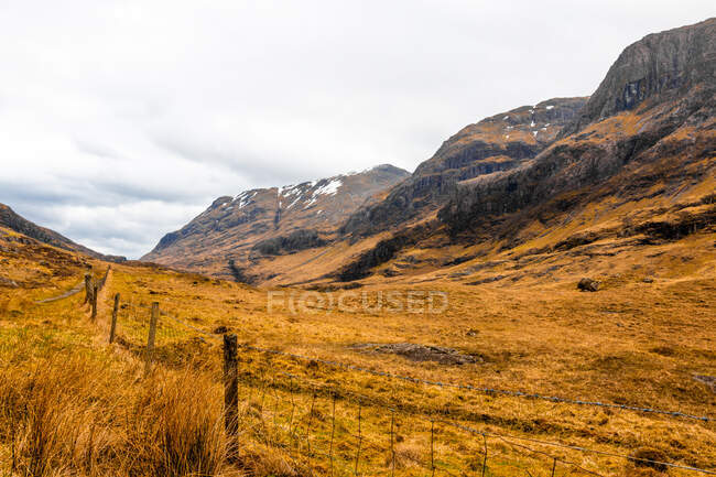 Вузька нерівна дорога проходить гористою місцевістю з сухою травою серед скелястих гір у похмурий весняний день у Шотландському нагір