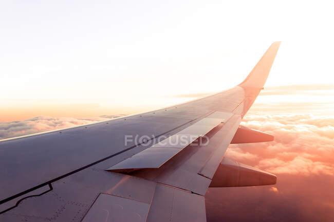Vista da janela de asa de aeronaves modernas voando sobre nuvens densas durante o pôr do sol — Fotografia de Stock
