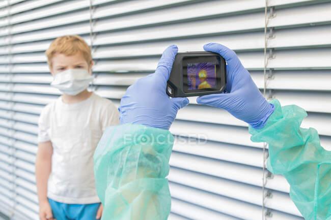 Нерозпізнаваний медік у захисних рукавицях та уніформі з використанням камери теплового зображення для перевірки температури дитини на вулиці під час спалаху коронавірусу. — стокове фото