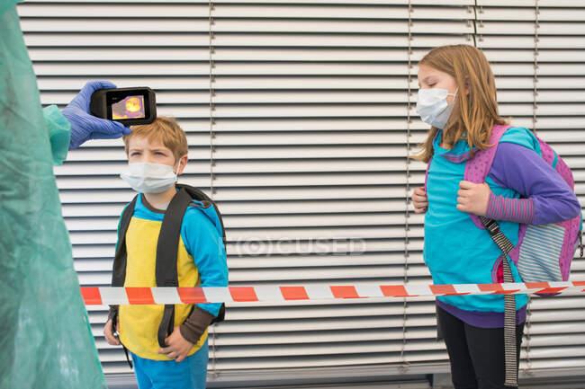 Erntehelfer in Schutzuniform mit Wärmebildkamera zur Kontrolle der Temperatur von Kindern in chirurgischen Masken auf der Straße während der COVID 19 Epidemie — Stockfoto