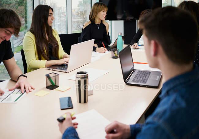 Focado jovens colegas ocupados em roupas casuais usando gadgets e fazer anotações enquanto trabalham juntos à mesa no espaço de co-trabalho contemporâneo — Fotografia de Stock