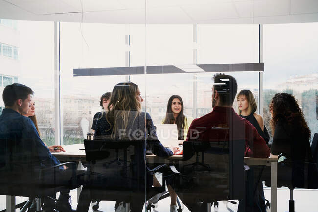 Focused young busy colleagues in casual clothes using gadgets and making notes while working together at table in contemporary coworking space — Stock Photo