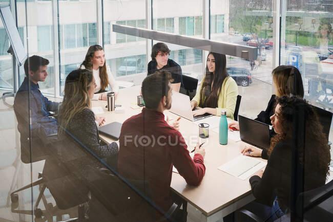 Сосредоточили внимание молодых занятых коллег в повседневной одежде, используя гаджеты и делая заметки, работая вместе за столом в современном коворкинговом пространстве. — стоковое фото