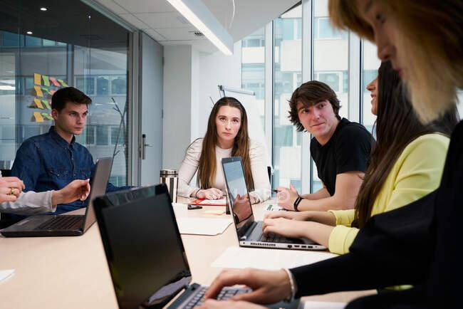 Vista laterale del raccolto femminile che lavora su laptop e prende appunti su carta mentre si siede a tavola con un gruppo di colleghi in un moderno spazio di coworking — Foto stock