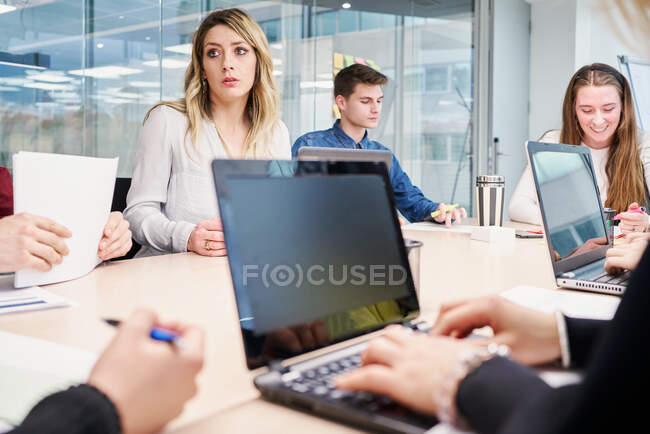 Side view of crop female working on laptop and taking notes on paper while sitting at table with group of colleagues in modern coworking space — Stock Photo