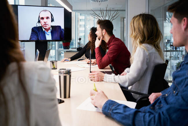 Group of young coworkers in casual clothes gathering around table and communicating with male partner during video conference in modern conference room — Stock Photo
