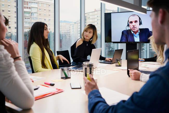 Gruppo di giovani colleghi in abiti casual che si riuniscono attorno al tavolo e comunicano con il partner maschile durante la videoconferenza nella moderna sala conferenze — Foto stock