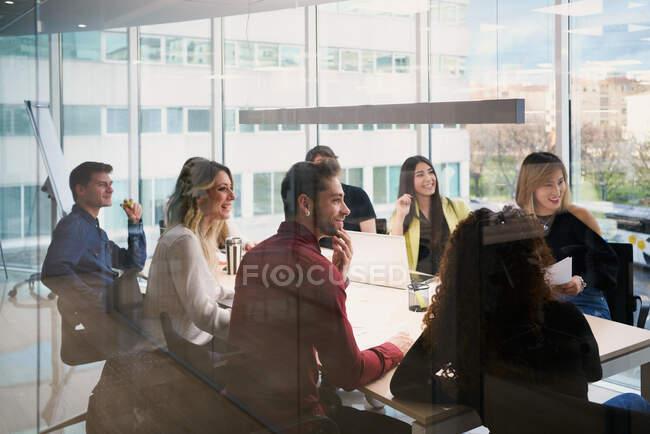 Зосереджувалися на роботі з молодими колегами в повсякденному одязі, використовуючи технічні новинки і роблячи нотатки, працюючи разом за столом у сучасному робочому місці. — стокове фото