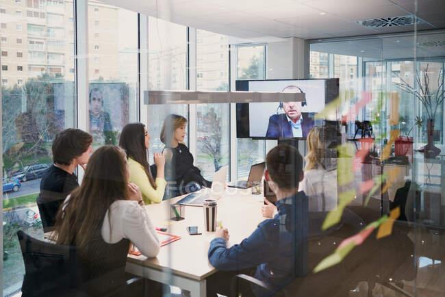 Группа молодых сотрудников в повседневной одежде собирается за столом и общается с партнером-мужчиной во время видеоконференции в современном конференц-зале — стоковое фото