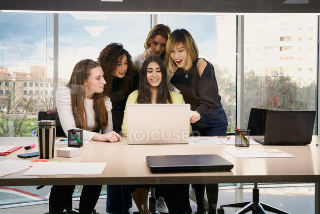 Group of focused young multiracial female colleagues in casual clothes gathering around laptop and watching business information while working together in modern workspace — Stock Photo