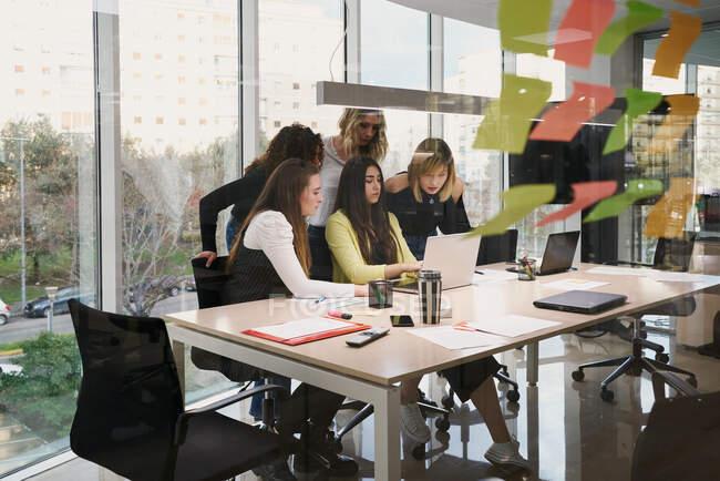 Группа молодых многорасовых коллег-женщин в повседневной одежде собирается вокруг ноутбука и наблюдает за деловой информацией, работая вместе в современном рабочем пространстве — стоковое фото