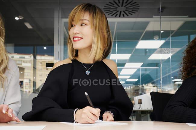 Angolo basso di elegante giovane imprenditrice asiatica che prende appunti su carta mentre si siede a tavola in un moderno spazio di lavoro durante l'incontro d'affari con i colleghi — Foto stock